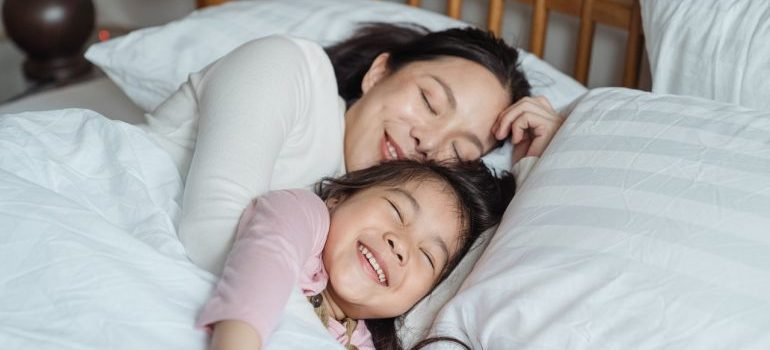 Mother and daughter resting in bed after relocating with some of the best local movers DC area has.