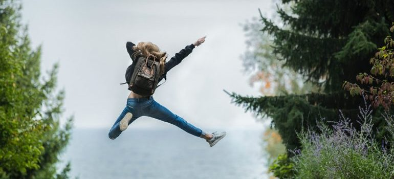 Excited girl with a backpack mid-jump.