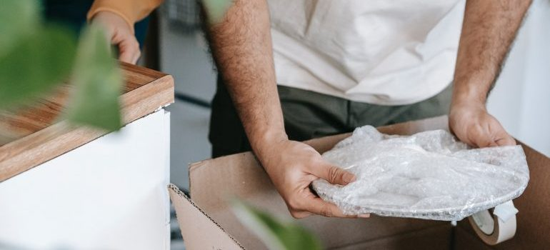 A man packing wrapped plates in the cardboard box.