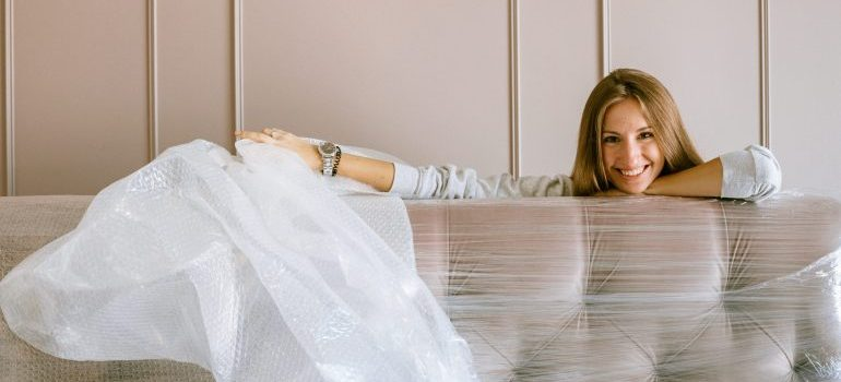 A woman next to a shrink wrapped sofa