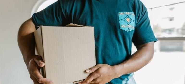 A man in a blue tshirt holding a cardboard box.