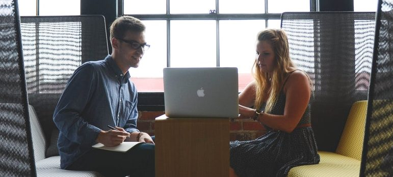 Two people using a laptop