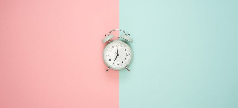A clock on a pink and blue surface.
