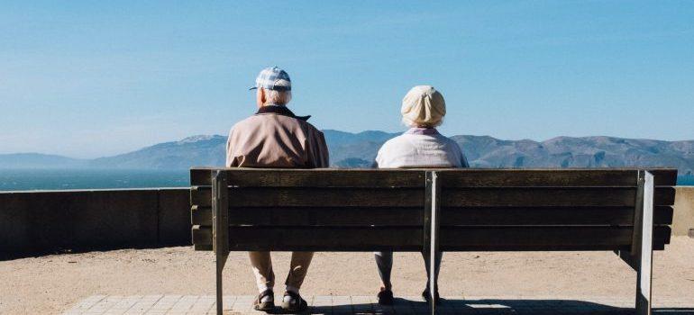 Two seniors sitting on a bench enjoying the wonderful view