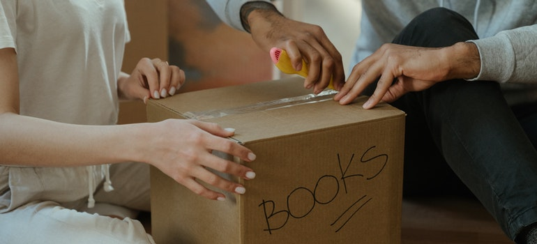 Two people are packing books into boxes before moving to Germantown MD.