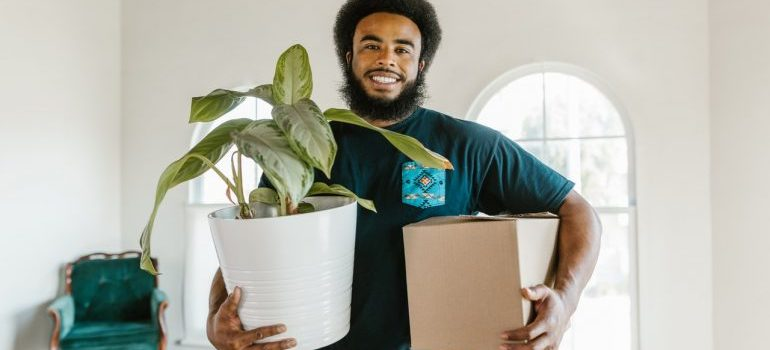 Potomac MD mover holding a box and a plant