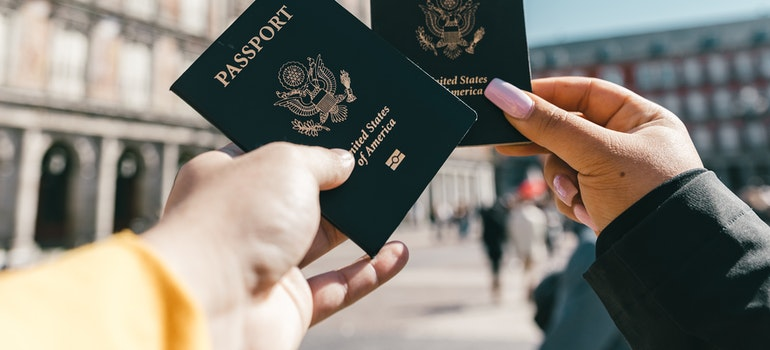 Two different hands are holding passports.