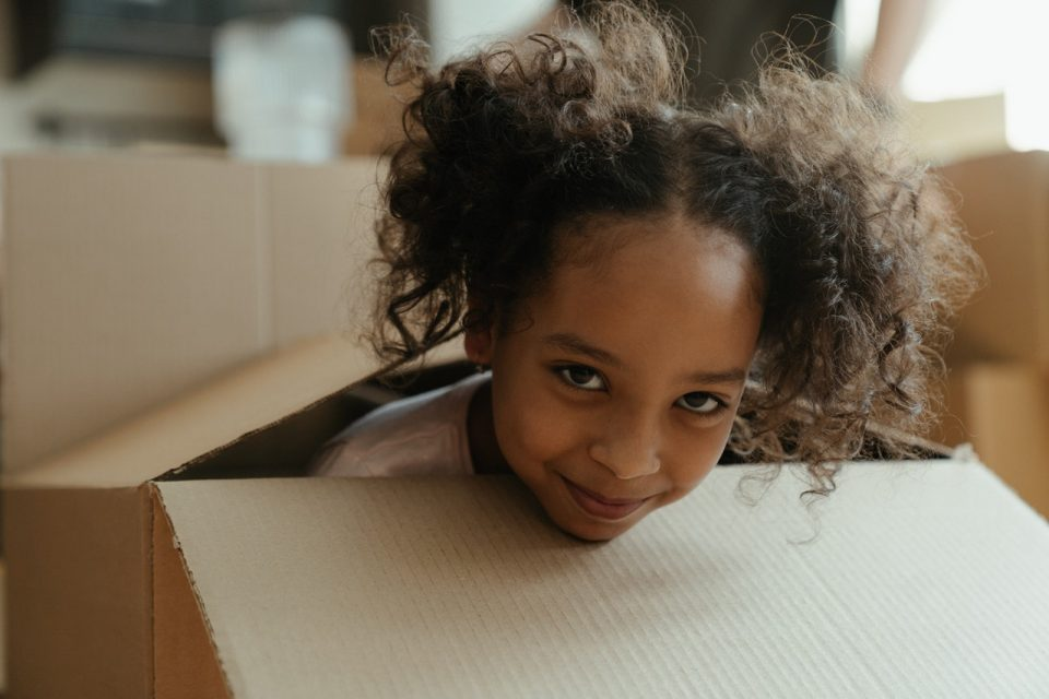 kid peaking out of a moving box