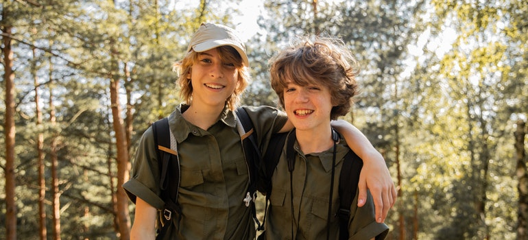 Two boys hiking across a forest.