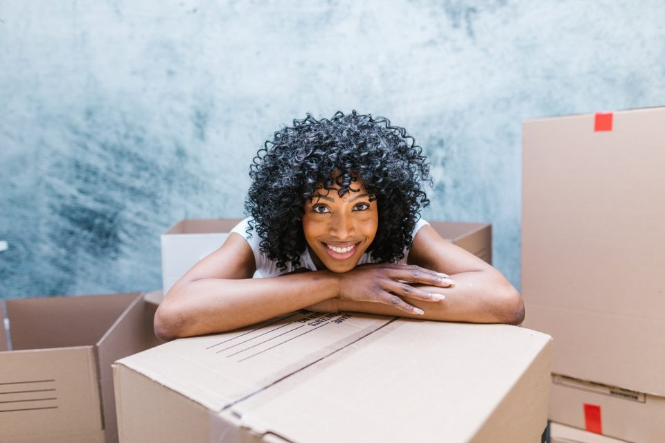 woman smiling over moving box
