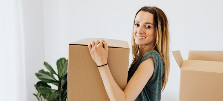 The girl holding the box with the packed things.