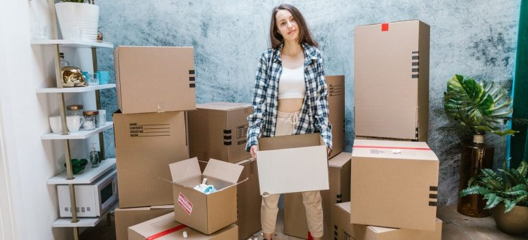 a woman holding a cardboard box while standing in between them