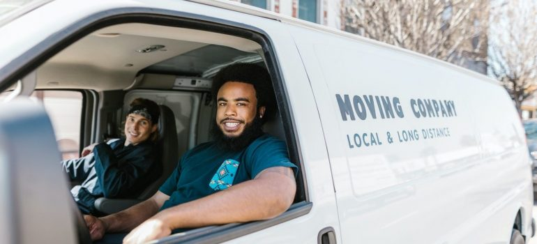 """two men sitting in a white van that say """"Moving Company"""""""