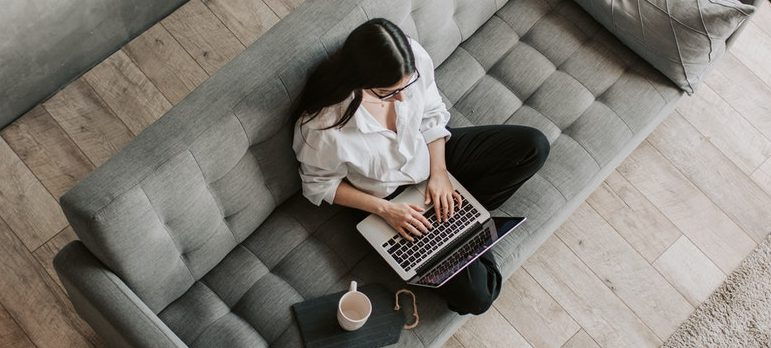 a woman using laptop on couch