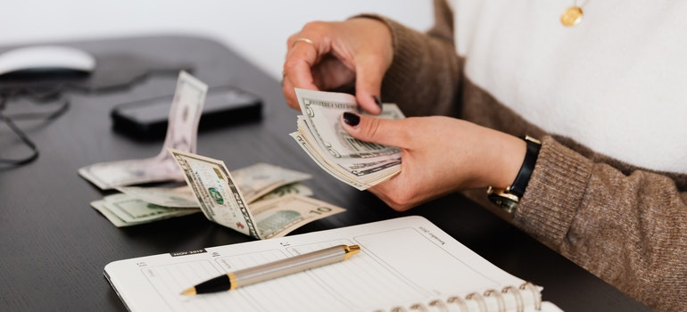 A woman counting money thinking about moving myths