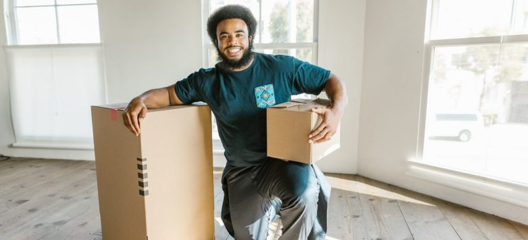 a man working for a moving company kneeling next to cardboard boxes