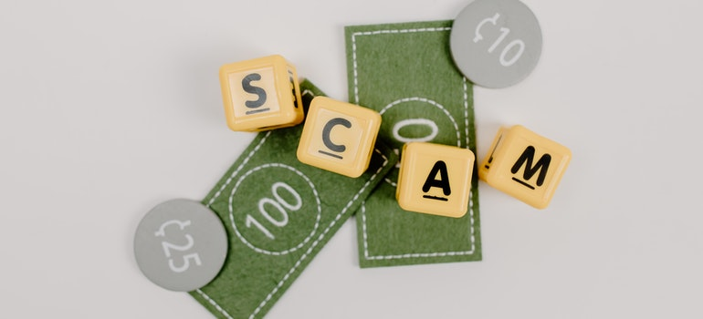 """cubes with letters on them form the word """"SCAM""""."""
